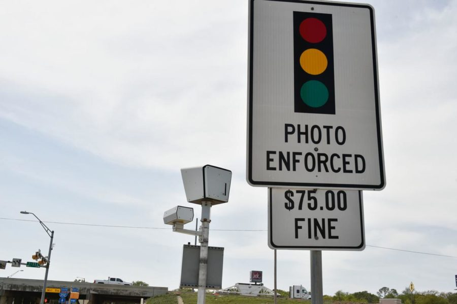 A red light camera and notification sign.