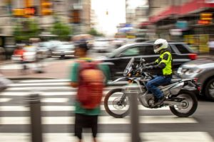 Motorcycle and pedestrian in traffic. Photo credit: Revzilla.com